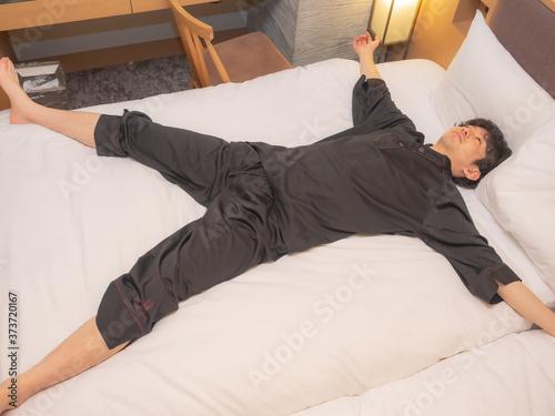 Fotografia ベットに寝転ぶ男性