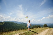 Little School Age Boy Running Down The Slope With Kite In The Sun. Sunny Summer Or Spring Day At Sunset. Active Outdoor Games And Leisure. Mountain Landscape With Hills And Coniferous Trees.