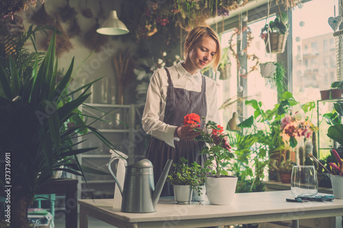 Lady Takes Professional Look on Plant Before Selling. Billede på lærred