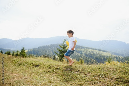 Fotografie, Tablou Child pilot aviator with airplane dreams of traveling in summer in nature