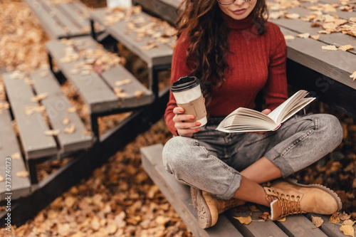Beautiful woman in cozy outfit reading book and drink coffee sitting on wooden bench in autumn park Canvas Print