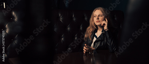 Fotografering Wide angle shot of young girl sitting alone in a pub with a glass of whiskey in hand and a pensive look