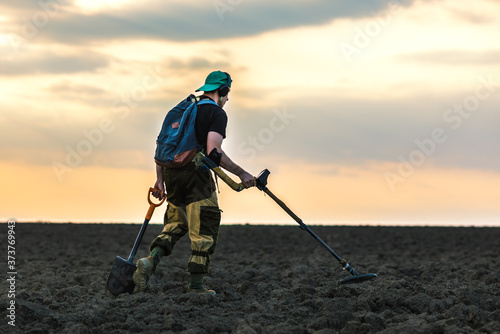 Photo Silhouette of a man with a metal detector at sunset