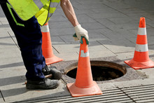Worker Over The Open Sewer Hatch On A Street Near The Traffic Cones. Concept Of Repair Of Sewage, Underground Utilities, Water Supply System, Cable Laying, Water Pipe Accident