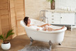 A attractive girl relaxes in the bathroom and rests against the backdrop of a beautiful light interior. Spa treatments for beauty and health with skin care