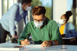 College student wearing protective face mask while writing exam in the classroom.