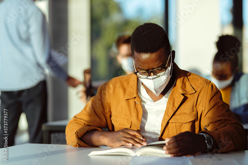 Fényképezés African American college student with face mask reading a book in the classroom