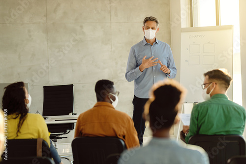 Cuadros en Lienzo Mid adult teacher with protective face masks talking to a group of university students in lecture hall
