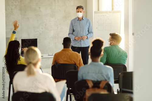Mid adult professor with a face mask holding a class to his students at lecture hall Fototapeta