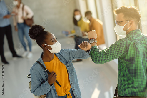 Happy university students greeting with elbow while wearing protective face masks Fotobehang