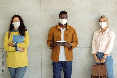 Photo Multi-ethnic group of college students with protective face masks against the wall