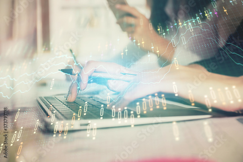 Multi exposure of woman hands typing on computer and financial graph hologram drawing Fototapeta