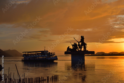 Obraz Silhouette of Lachit Borphukan statue during sunset with a ship passing in background in river brahmaputra.	 - fototapety do salonu
