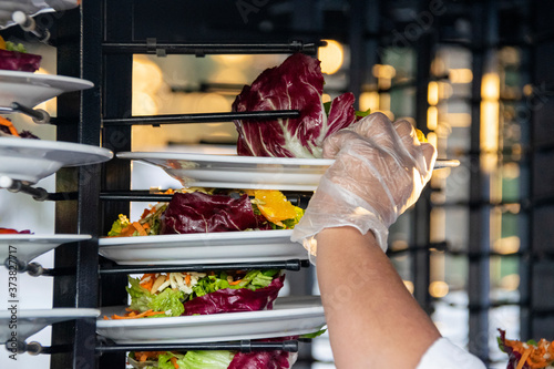 Photo Man's hand accommodating group of salads served for mass event in Latin America,