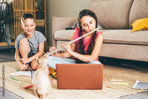 Fotografia, Obraz Little boy in grey t-shirt draws in paper notebook during teenage girl playing s