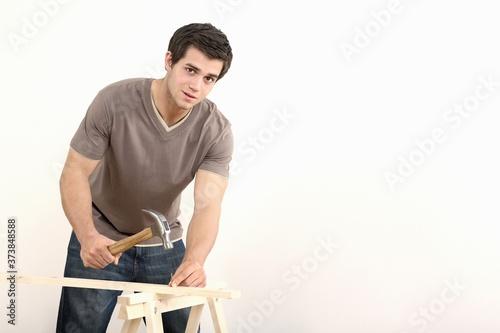 Fotografie, Obraz Man hammering nail into wood