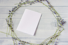 Fresh Purple Lavender Flowers On A White Wooden Table Background Laid Out In Form Of Round Frame With A Blank White Sheet Of Paper In Center With Copy Space.Floral Composition. Mock Up,top View,flat