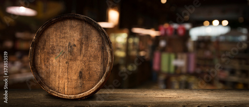 Wooden barrel on a table and textured background Fototapeta
