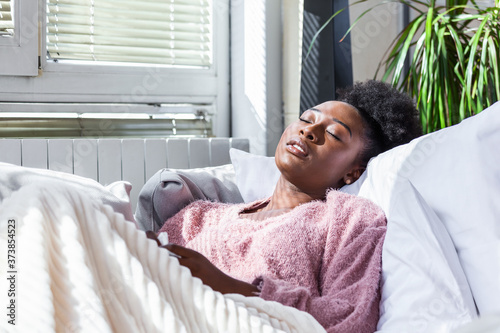 Fotografía Sick young african woman feeling cold covered with blanket sit on bed, ill black