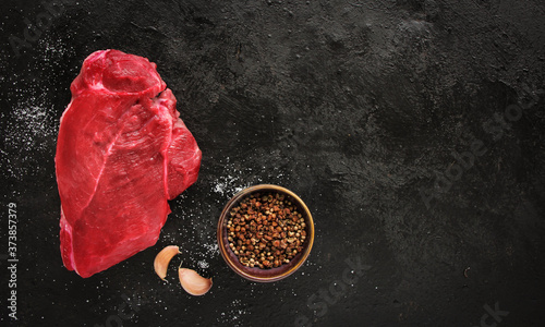 Leinwand Poster Raw beef steak with spices on a dark slate, stone or concrete background