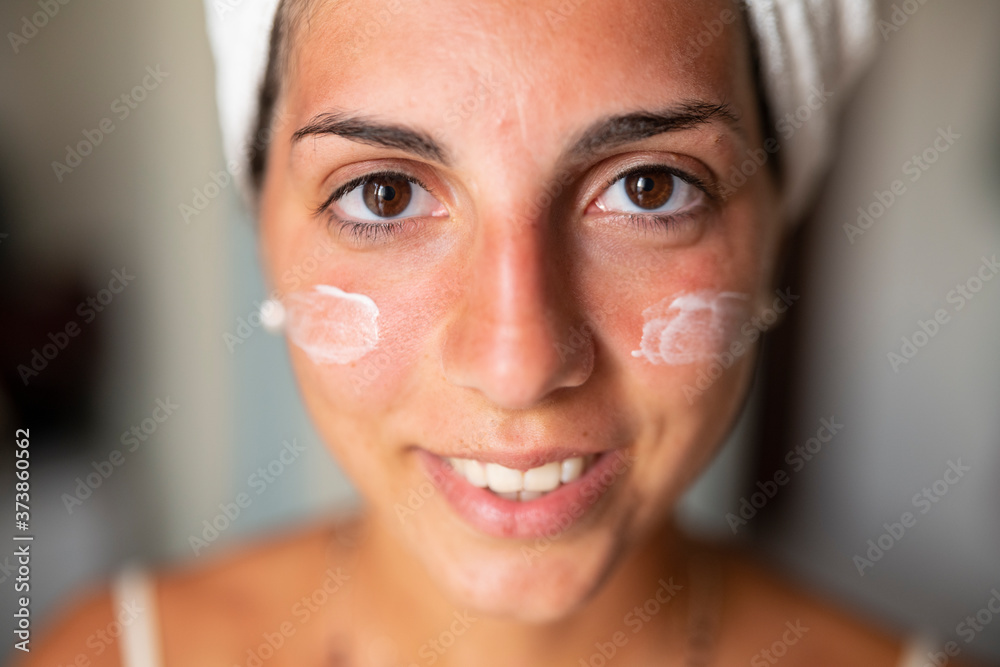 Fototapeta Close up shot of an young happy woman with perfect skin just cleaned from impurities with day or night cream applied on her face is smiling in camera in a bathroom.