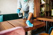 canvas print picture - Handsome middle age waiter cleaning and disinfecting restaurant table for next customer. Corona virus and small business is open for work concept.