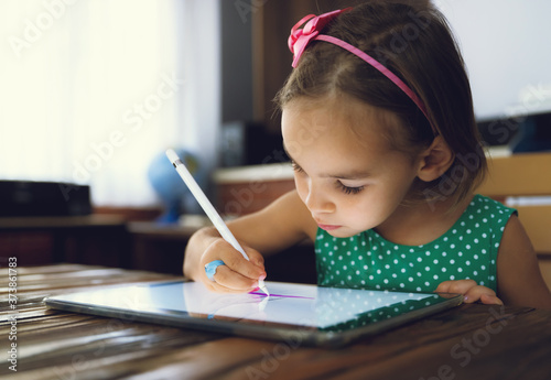 Fotografia, Obraz Child Girl Is Drawing And Painting Pictures Using Digital Tablet