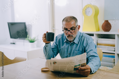 middle aged man reading newspaper at home Fototapeta