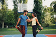 canvas print picture - Beautiful young couple enjoying together and playing on basketball court. Bright sunny summer day.