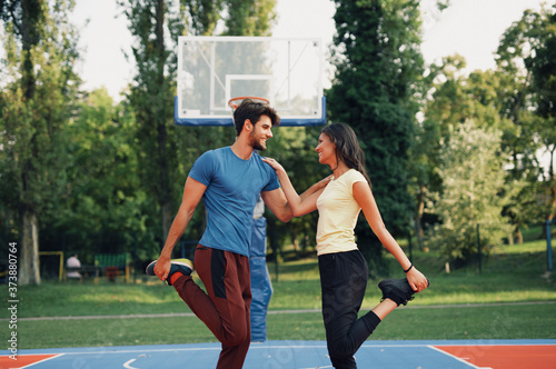 Beautiful young couple enjoying together and playing on basketball court Slika na platnu