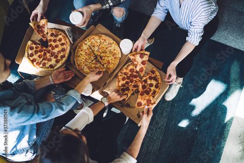 Obraz na plátně Unrecognizable friends eating pizza during party