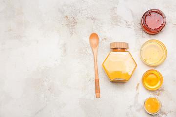 Assortment of tasty honey on grey background