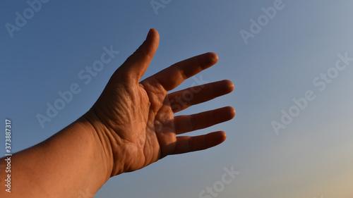 Fototapeta Frau mittleren Alters, Handfläche vor blauem Himmel, Hand von innen als Handzeic