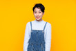 Young Asian girl in overalls over isolated yellow background with surprise facial expression