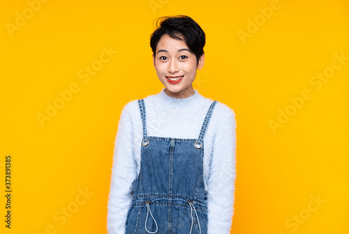 Photo Young Asian girl in overalls over isolated yellow background with surprise facia