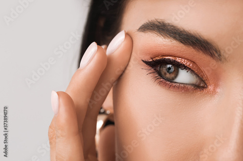 Fototapeta Young woman with beautiful eyeshadows on light background, closeup
