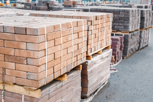 pallets and packages of freshly produced red bricks in a construction warehouse on the street Canvas Print