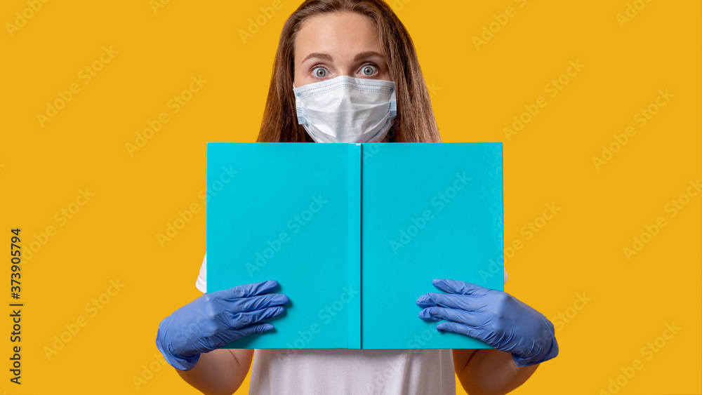 Fototapeta School reopen. Quarantine class. Scared female student in protecting face mask gloves holding open blue book isolated on bright yellow copy space. COVID-19 outbreak. Hygiene measures. Safe education.