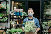 Small Business And Start Of Working Day. Man In Protective Mask Takes Out Box Of Plants Outside