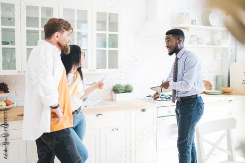 Tela Male realtor demonstrating kitchen to couple