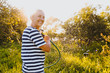 canvas print picture - Happy elderly senior woman having fun watering plants with hose in summer garden. Drops of water in backlight. Farming, gardening, agriculture, old age people. Growing organic vegetables on farm