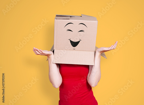 Slika na platnu Person with cardboard box on its head and a smiling face stretching its hands ou