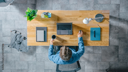 Foto Top View Shot: Businessman Sitting at the Wooden Desk Works on a Laptop in his Home Office