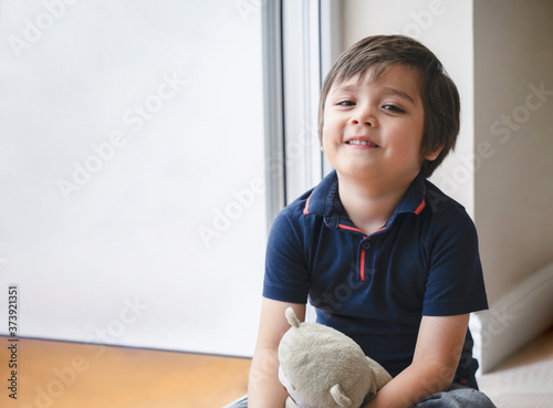 Stampa su Tela PPortrait of happy kid sitting on wooden floor playing with teddy bear, Cute boy play with his soft toy, Positive child relaxing at home