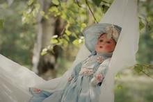 An Antique Doll Chilling In The Swing In The Birch Shade During The Late Summer Afternoon