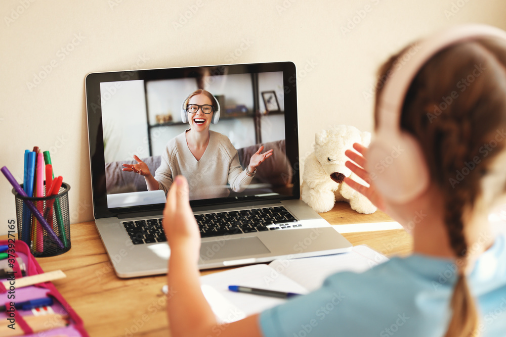 Fototapeta schoolgirl wearing headphones communicates via video link with an online teacher sitting at home