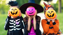 Happy Halloween! Funny Children In Carnival Costumes Hide Their Heads Behind Buckets   Pumpkins Outdoors.