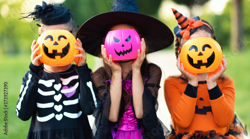 Fényképezés Happy Halloween! funny children in carnival costumes hide their heads behind buckets   pumpkins outdoors