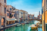 Fototapeta Uliczki - Chioggia cityscape with narrow water canal Vena with moored multicolored boats between old colorful buildings and brick bridge, blue sky background in summer day, Veneto Region, Northern Italy