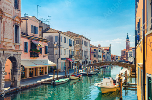 Fotomural Chioggia cityscape with narrow water canal Vena with moored multicolored boats b